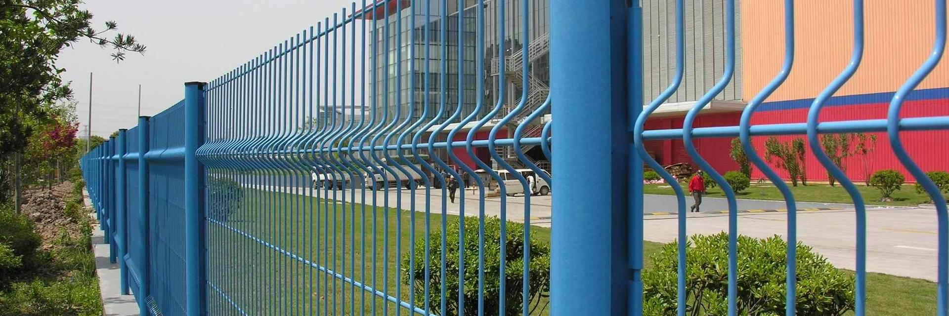 Blue curvy fence panels are installed along the factory.