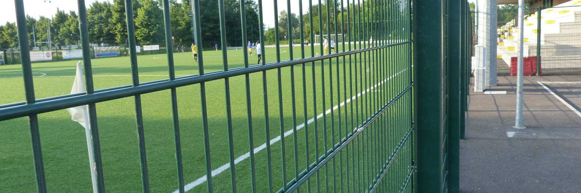 Dark green double wire fences are installed along the football field.