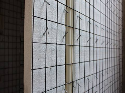 A vertical 3D panel with welded wire mesh outside and foaming polystyrene inside.