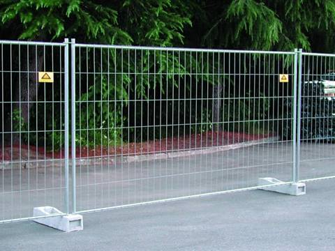 The Australia portable fence is installed in the street behind a park.