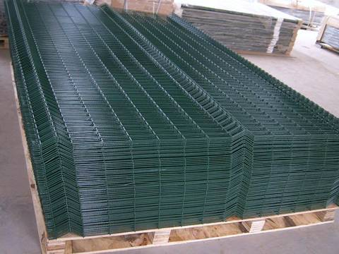 Many sheets of PVC coated dark green welded mesh panel are placed on wooden pallet.