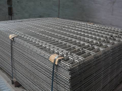 A stack of reinforcing mesh is packed with metal belt in workshop.