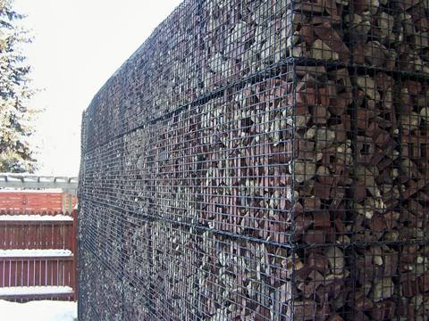 A heavy duty welded mesh gabion box with uniform mesh openings is full of rocks.