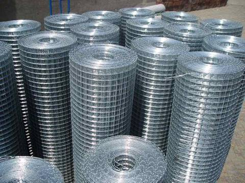 Several rolls of galvanized welded wire mesh rolls on the ground.