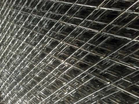 Many sheets of welded razor barbed wire with diamond holes.