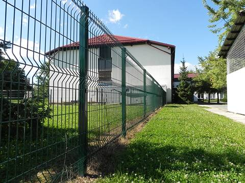 A PVC coated green welded wire mesh as fence is around a white house.