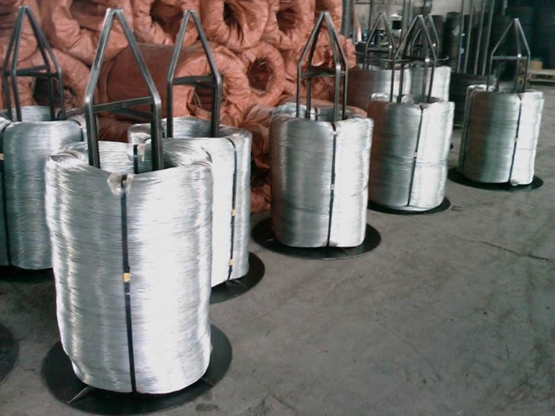 Some coils of electro galvanized wire are in coils are placed on the metal bracket and some coils are in orange plastic woven bag.