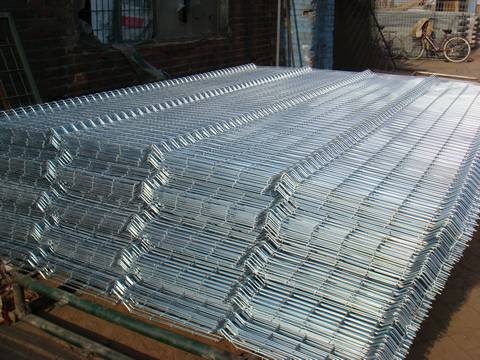 Many sheets of galvanized welded wire mesh fence are placed together.