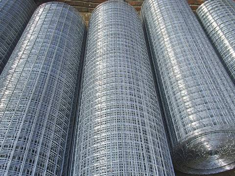 Five rolls of dipped galvanized welded wire mesh with shiny surface are placed together.