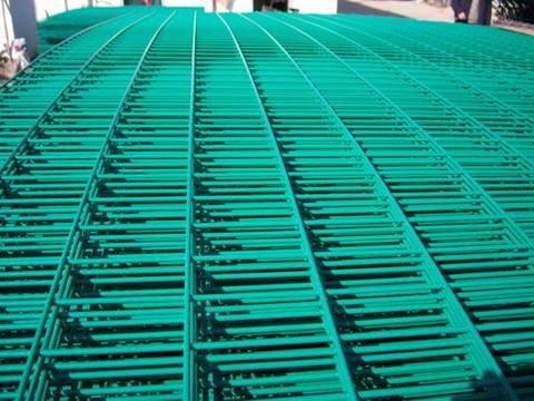 Many sheets of PVC coated light green welded mesh panel with rectangular holes.