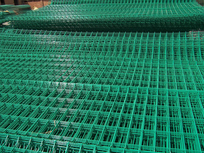 Many sheets of PVC coated green welded wire mesh with rectangular holes.