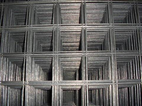 Many sheets of indented reinforcing mesh with square holes.