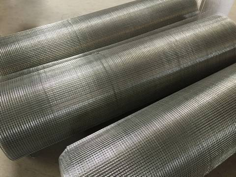 Three lying rolls of stainless steel welded wire mesh on the ground.