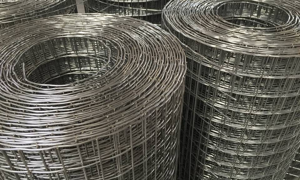 Several standing rolls of stainless steel welded wire mesh are in workshop.