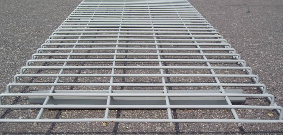 A sheet of gray uninstalled wire mesh decking with rectangular holes and smooth surface.