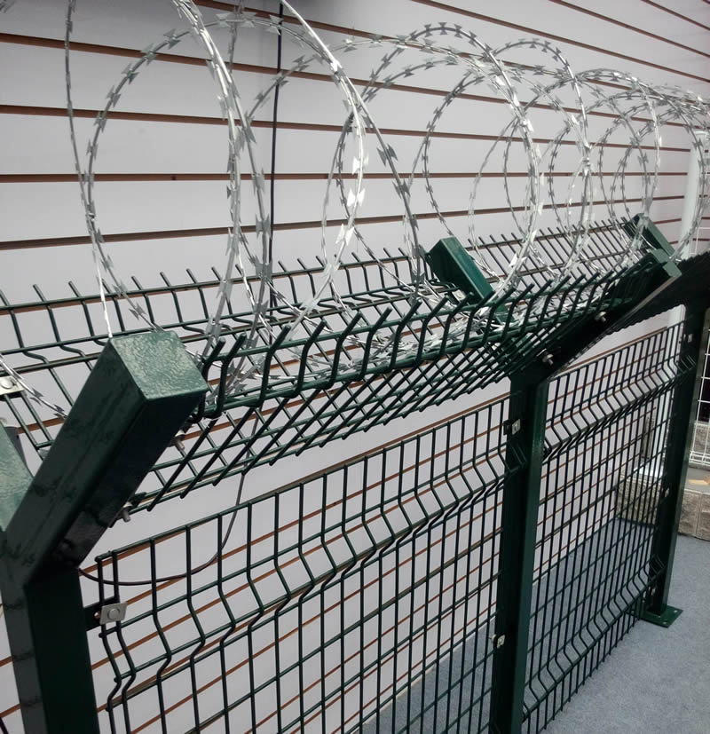 Galvanized concertina razor wire on top of PVC coated dark green welded wire mesh fence by Y shaped crank arm.