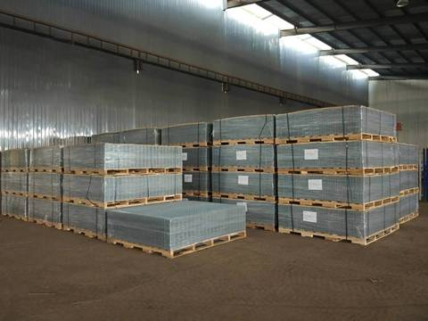 There are several pallets of welded wire mesh panel in the warehouse