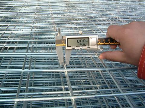 A people is measuring the wire diameter of welded wire mesh with ruler.