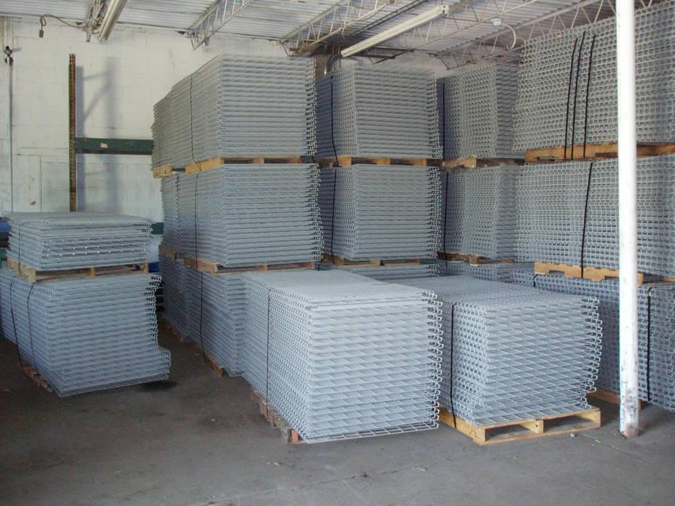 Many stacks of uninstalled wire mesh decking placed on the wooden pallet are in workshop.